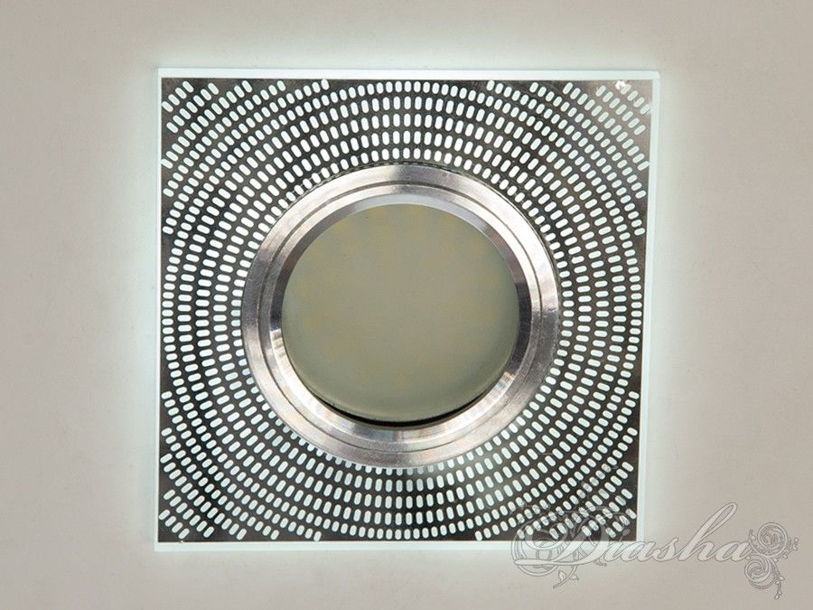 Светильник оснащен встроенным LED модулем 3W, что дает ему возможность распределения на три включения (двойной выключатель): лампа, встроенная подсветка, и одновременно и лампа и подсветка. Режим подсветки можно использовать, как самостоятельный заполняющий свет. Основная лампа стандарта MR-16 наоборот даёт основную часть светового потока строго вниз - этот режим хорош для подсветки стола/рабочей поверхности, чтения и тд.Большая часть света подсветки отражаясь от декоративной металлической маски, рассеивается параллельно потолку. Оставшаяся часть светит узором через маску. Теневая металлическая маска способна создать четкий геометрический рисунок даже для такого яркого источника света как LED подсветка. В отличии от хрустальных светильников и светильников из оптической смолы световой рисунок выглядит строго, а не набором случайных бликов.Точечные светильники просты и легки в установке, поэтому их монтирование не займет много времени и труда. Они запросто могут изменить пространство помещения. Если точечные светильники установить по периметру потолка, то он будет казаться выше, а сама комната – намного больше.Конструкция светильника идеально расчитана на использование с натяжными потолками.Для оптовых покупателей отпускается только ящиками по 50 шт.Лампа в комплект не входит.